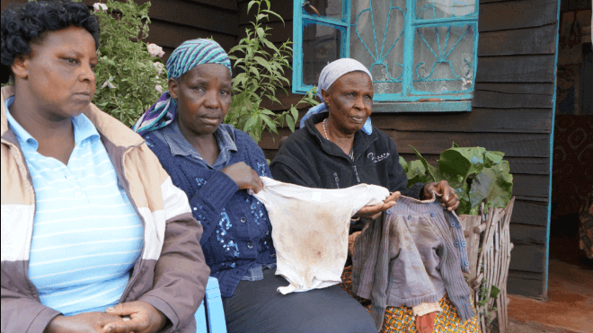 Lucy Njuguna (left) the grandmother of the 1 year and four months Nzuki Mutinda shows neighbours the cloths Mutinda was wearing when he was killed by their househelp.