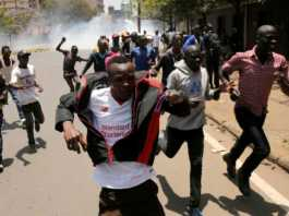 NASA supporters run as riot policemen fire tear gas to disperse them during a Nairobi protest for the sacking of IEBC officials, October 6, 2017. Photo / The Star