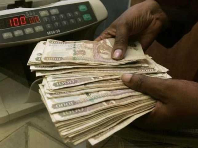 A currency dealer counts Kenya shillings at a money exchange counter in Nairobi . /The Star
