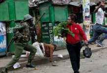 An anti-riot policeman attempts to disperse people from the street as a woman carrying vegetables walks past in Mathare slums, Nairobi, August 9, 2017. /The Star
