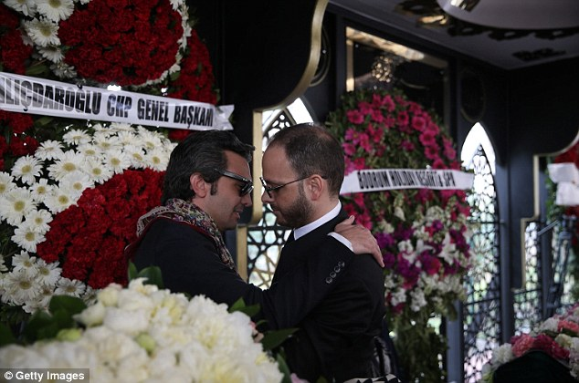 Left behind: Mr Gezer and Mr Urfali embrace and offer condolences to each other during the funeral ceremony at the Atakoy 5th Section Mosque in Istanbul