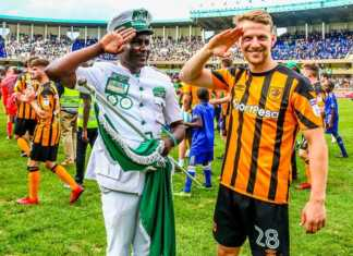Gor Mahia FC fan 'number 1' Jared 'Jaro Soja' Obonyo (left) and Hull City FC midfielder, Stephen Kingsley salute fans at the end of the international friendly at MISC, Kasarani on Sunday, May 13, 2016. PHOTO/AFP