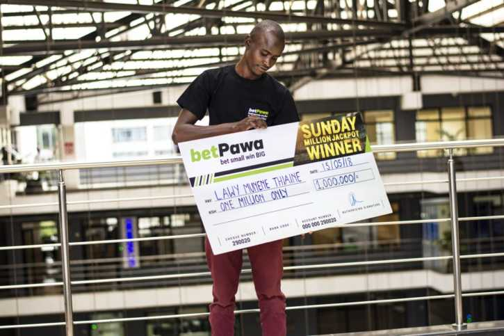 Lawy Munene from Meru displays his winner's cheque after winning betPawa jackpot last weekend /COURTESY