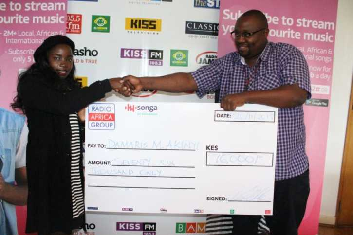 Brian Chege from Songa by Safaricom presents to Damaris her cheque of sh 76,000 for the #SongaNaMili competition