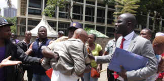 A court orderly rescues lawyer Simon Mburu from Ekeza Sacco members outside a Milimani court, Nairobi, on Thursday. /COLLINS KWEYU