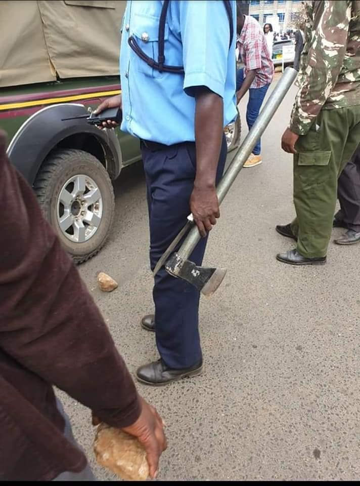Police carrying an axe and knife Kinuthia used to kill Ivy Wangeci