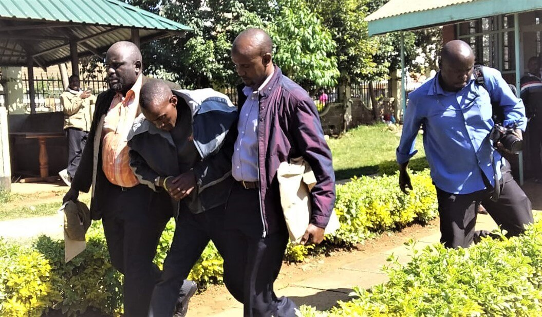 Joshua Ogachi, the prime suspect in the murder of a police officer in Eldoret, is supported by security officers when he was brought to court on Monday, September 16. He is suspected to have taken poison.