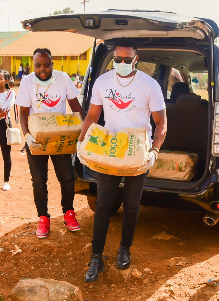 Members of Lucy Natasha's foundation carrying bales of maize flour.